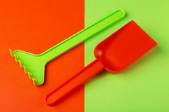 Colorful toy spade and rake on bright background. Copy space royalty free stock images