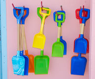 Colorful toy spades hanging on wall Stock Photos