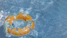 Colorful toy swimming tire at the pool stock images