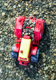 Colorful toy tractor and pebbles in the water Royalty Free Stock Photography