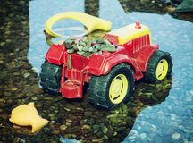 Colorful toy tractor reflected in the water Stock Images