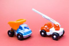 Colorful toy truck and fire truck on a pink background royalty free stock photography