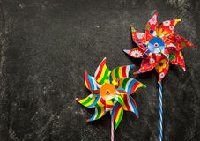 Colorful toy windmills on black - childhood Stock Images