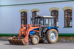 Colorful tractor with a bucket is near the house Stock Photos