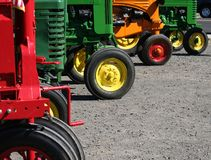 Colorful Tractors. Colorful vintage farm tractors lined up in a row royalty free stock photos
