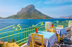 Colorful traditional Greek restaurant with view on sea and remot. E Island, Greece Royalty Free Stock Images