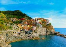 Colorful traditional houses on a rock over Mediterranean sea, Manarola, Cinque Terre, Italy Royalty Free Stock Photos