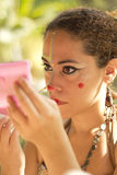 Colorful traditional makeup. NITEROI, BRAZIL - MAY 6, 2014: a woman getting her makeup before going on a street party Stock Photography