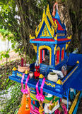 Colorful Traditional Thai outdoor spirit house shrine with flower garlands under the tree shade.  Stock Photo