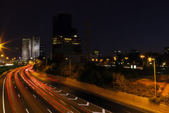 Highway River to Downtown. Colorful trails of light is all that remains from the swift highway traffic, rushing towards the downtown district of Tel-Aviv, Israel Royalty Free Stock Image