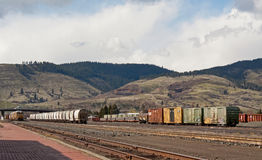 Colorful Trains Waiting In A Train Yard. Bright strings of trains wait in a train yard with the mountains in the background stock photography