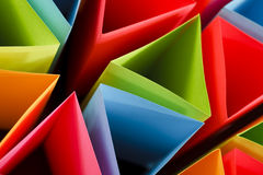 Colorful Triangles. Macro and abstract image of colored cardstock (blue,red,pink,yellow and green) with a triangular shape on a black background. Selective focus royalty free stock photos