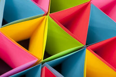 Colorful Triangles. Macro and abstract image of colored cardstock (blue,red,pink,yellow and green) with a triangular shape on a black background. Selective focus stock photos
