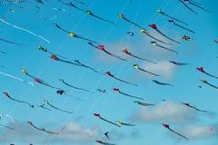 Colorful triangular kites fill the blue sky Stock Photos