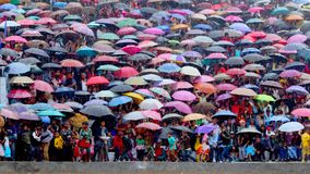 Colorful tribal local crowd with umbrellas in the rain. A crowd of people with many colorful umbrellas in the rain during a festival in Jiantia Hills in royalty free stock photo