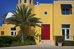Colorful Tropical Building. A sun-lit, colorful tropical building with bright red door and palm tree royalty free stock photos