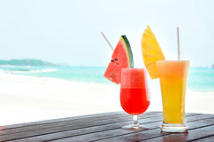 Colorful tropical fruit juice smoothies in the glasses. On beach background - soft focus stock photo