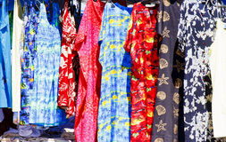 Colorful Tropical Garb in an Outdoor Flea Market. Colorful garments hanging in a stall at an outdoor flea market Royalty Free Stock Image