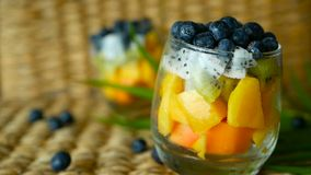 Colorful tropical mix salad in jar. Fresh various kind of raw organic berry and fruit in glass bowl. Healthy vegetarian stock video footage