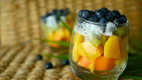 Colorful tropical mix salad in jar. Fresh various kind of raw organic berry and fruit in glass bowl. Healthy vegetarian. Eating, balanced, vegan diet. Rustic stock video footage