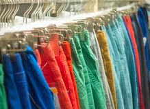 Colorful trousers hanging on sale in store Royalty Free Stock Photography