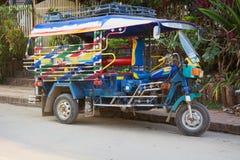 Colorful Tuk-Tuk Taxi Parked curbside in Luang Prabang, Laos Royalty Free Stock Photography