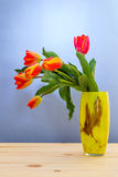 Colorful tulip on wooden table in yellow vase Royalty Free Stock Photos