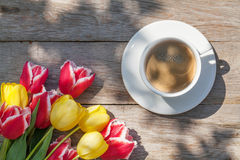 Colorful tulips and coffee cup on garden table Stock Photography