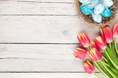 Colorful tulips and easter eggs in nest on wooden table Royalty Free Stock Photo
