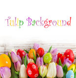 Colorful tulips with easter eggs on wooden table. Royalty Free Stock Photos