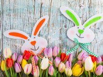 Colorful tulips with easter eggs on wooden table. Stock Photos