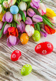 Colorful tulips with easter eggs on wooden table. Stock Images