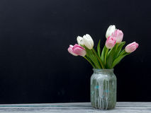 Colorful tulips flowers on black board background wooden table. Top view with copy space Stock Photos