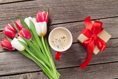 Colorful tulips, gift box and red coffee cup Royalty Free Stock Photos