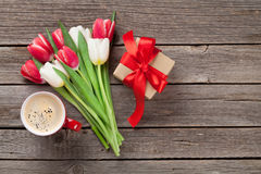 Colorful tulips, gift box and red coffee cup royalty free stock images