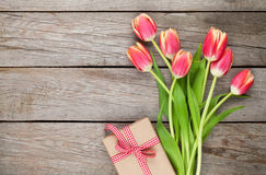 Colorful tulips and gift box on wooden table Stock Photography