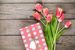 Colorful tulips and gift box on wooden table Royalty Free Stock Photo