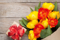 Colorful tulips and gift box on wooden table Stock Photo