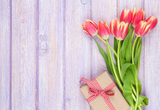 Colorful tulips and gift box on wooden table Stock Images