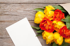 Colorful tulips and greeting card on wooden table Royalty Free Stock Photo