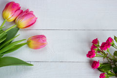Colorful tulips with miniature roses on wooden table. Stock Image