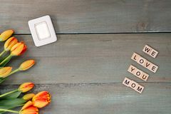 Colorful tulips and small picture frame on weathered green plank. S. Tile letters with sentiment for Mother`s Day Royalty Free Stock Photos