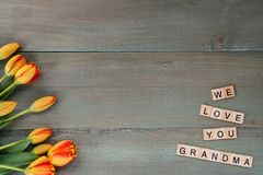 Colorful tulips on weathered green planks. Tile letters with sen. Timent for Mother`s Day Stock Photo