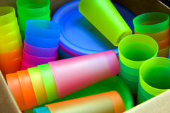 Colorful Tumblers. Collection of colorful tumblers and plates in a box at a tag sale Stock Photos