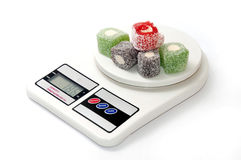 Colorful turkish delight on digital kitchen scale Royalty Free Stock Image