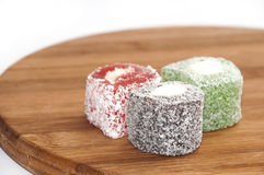 Colorful turkish delight on the kitchen wooden board Stock Images
