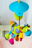 Colorful turning cow baby toy over the bed. Colorful turning cow baby toy over bed Royalty Free Stock Photography