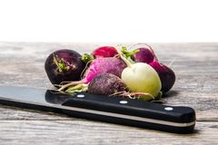Colorful turnips on a wooden cutting board. Colorful turnips waiting to be cut on a wooden cutting board against a white background Stock Image
