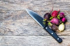 Colorful turnips on a wooden cutting board. Colorful turnips waiting to be cut on a wooden cutting board Royalty Free Stock Photo