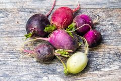 Colorful turnips on a wooden cutting board.  Stock Images